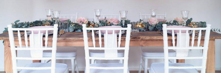 rustikale Holztische mit weißen Tiffany Stühlen und hängenden Laternen