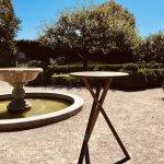 Stehtisch aus Holz im Garten mit Springbrunnen