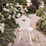 Weißer Brautstuhl inmitten von weißen Hortensien