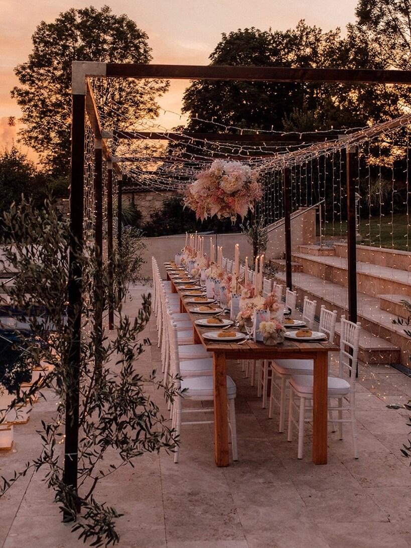Tisch-Holzkonstruktion mit Lichterhimmel für Gartenhochzeit
