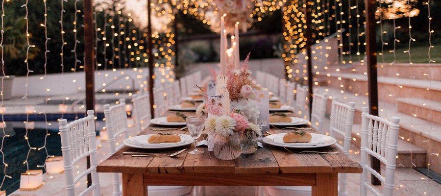 Holzkonstruktion mit Lichterketten bei Hochzeitsfeier im Garten