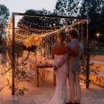 Brautpaar vor Hochzeitstafel mit Lichterhimmel im Garten
