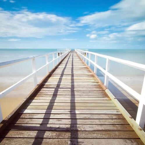 weißer Steg ins Meer mit strahlend blauem Himmel