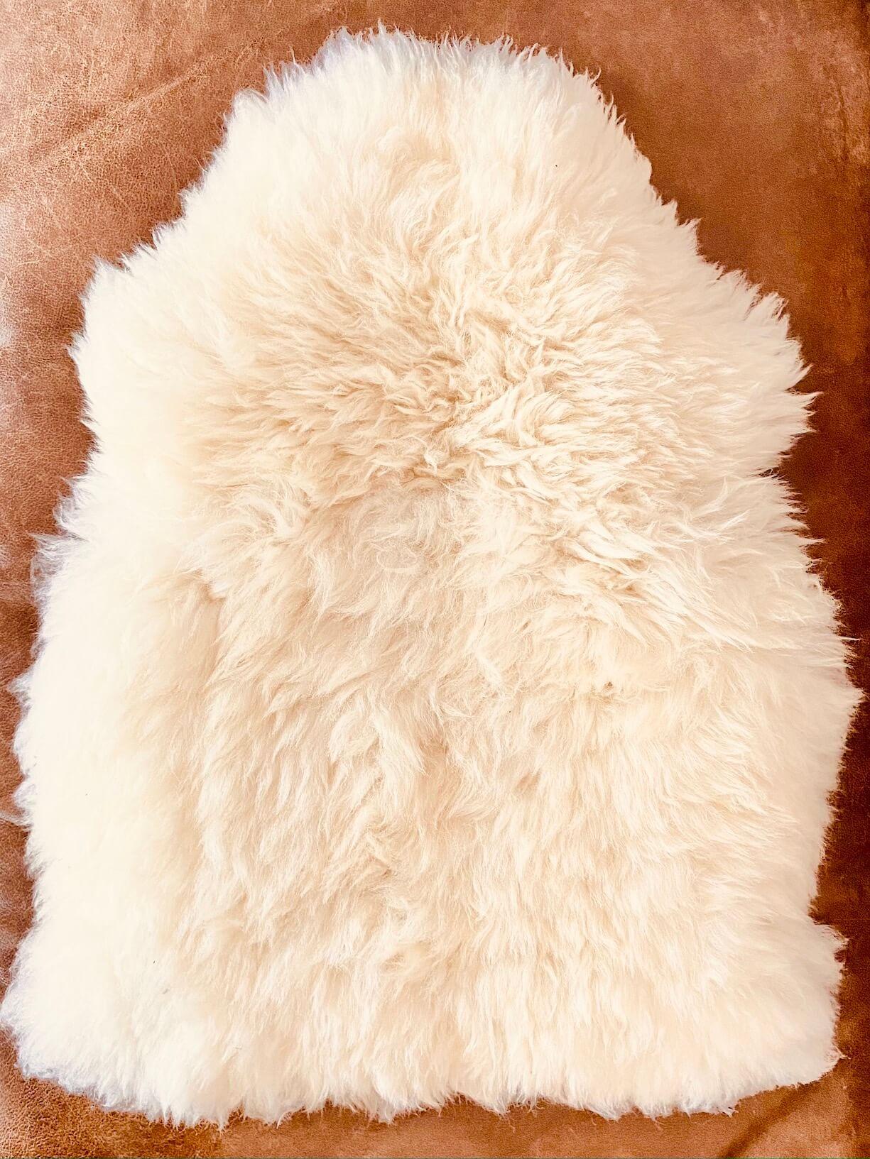 Schafsfell auf braunem Ledersofa