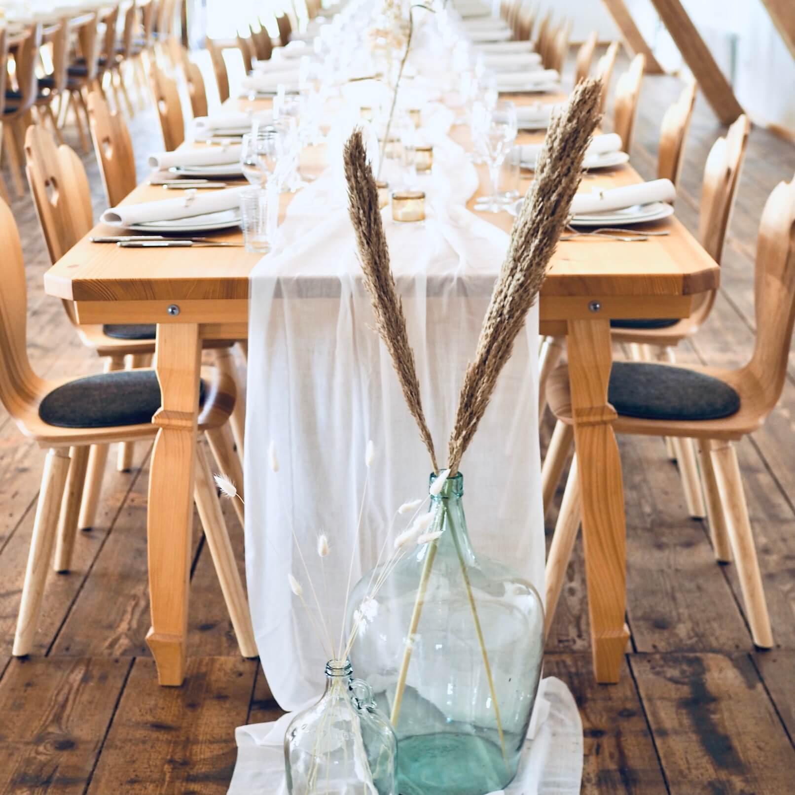 weißer Tischläufer auf Holztisch bei Hochzeit