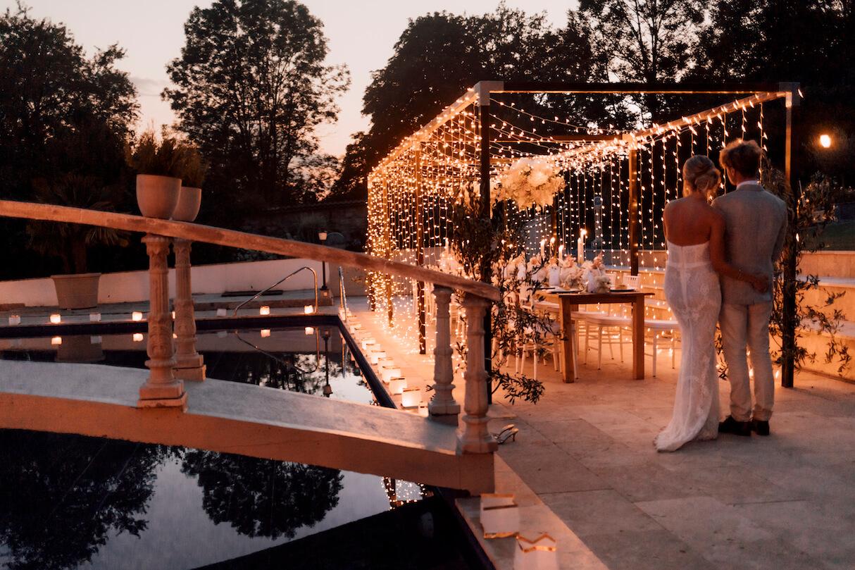 Dinner Frame mit Lichterhimmel über gedeckter Tafel mit staunendem Brautpaar